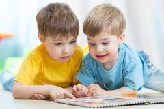 Children read together book lying on floor in Stock Photography