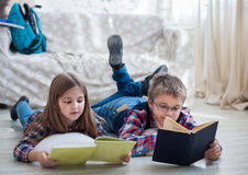 Children readind book in living room. Brother and sister readind book in living room Stock Photo