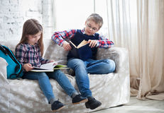 Children readind book in living room Stock Images