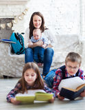 Children readind books in living room. Son and daughter with their mother and little brother siting on the sofa. Children readind books in living room. Focus on royalty free stock photography