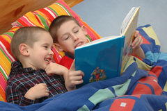 Children are reading the book. Older brother is reading the Bible for his younger brother Royalty Free Stock Image