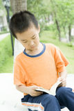 A children  reading book. In garden Stock Photo