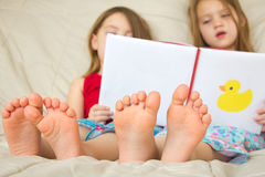 Children reading a book in bed. Young children reading a book in bed Royalty Free Stock Photography