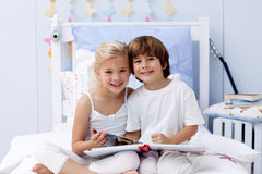 Children reading a book in bedroom. Smiling children reading a book in bedroom Royalty Free Stock Image