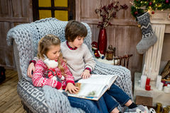 Children reading book. Engrossed children sitting on grey armchair and reading book Stock Photos
