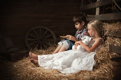 Children reading the book on the hay in the barn Stock Photography