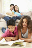 Children Reading Book At Home. Hispanic Children Reading Book At Home, Parents In Background Stock Photos