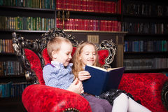 Children reading book at home. Boy and girl in library Stock Image