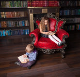 Children reading book at home. Boy and girl in library Stock Images