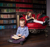 Children reading book at home. Boy and girl in library Stock Photography