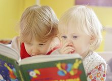 Children reading book indoor. Two children reading book indoor Royalty Free Stock Image