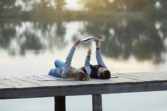 Children reading book on the lake royalty free stock image