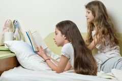 Children are reading a book lying in bed at home. The elder girl reads aloud to the younger sister.  Stock Image