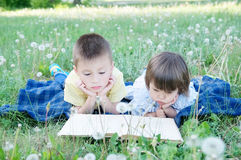 Children reading book lying on stomach outdoor among dandelion in park, cute children education and development. Back to school co Stock Images