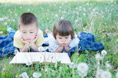 Children reading book lying on stomach outdoor among dandelion in park, cute children education and development. Back to school co. Ncept Stock Photo