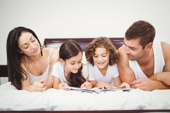 Children reading book with parents at home. Close-up of children reading book with parents on bed at home Stock Photography
