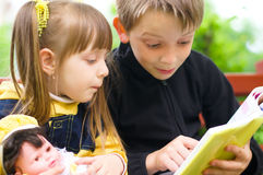 Children reading the book. At the park Stock Photo