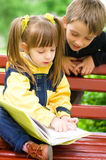 Children reading the book. At the park Royalty Free Stock Photo