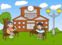 Children reading a book and playing guitar in front of their school cartoon Royalty Free Stock Image