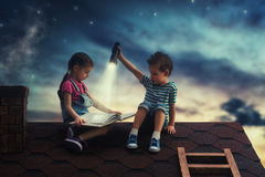 Children reading a book. Sitting on the roof of the house. Boy and girl reading by the light of a flashlight at night Stock Image