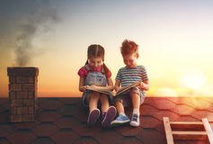 Children reading a book. Sitting on the roof of the house. Boy and girl reading by the light of sunset Stock Photo