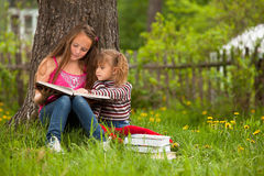 Children reading the book in summer park
