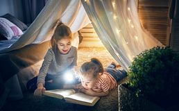 Children are reading a book. Two cute little children are reading a book with flashlights in tent. Happy girls playing at home. Funny lovely kids having fun in Royalty Free Stock Photography