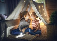 Children are reading a book. Two cute little children are reading a book with flashlights in tent. Happy girls playing at home. Funny lovely kids having fun in Stock Images