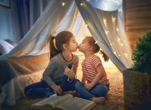 Children are reading a book. Two cute little children are reading a book with flashlights in tent. Happy girls playing at home. Funny lovely kids having fun in Royalty Free Stock Photos