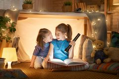 Children are reading a book. Two cute little children are reading a book with flashlights in tent. Happy girls playing at home. Funny lovely kids having fun in stock image