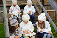 Children reading Books Outdoors Royalty Free Stock Photo