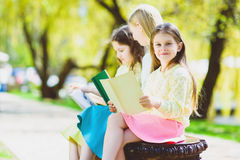 Children reading books at park. Girls sitting against trees and lake outdoor Royalty Free Stock Photos