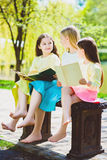 Children reading books at park. Girls sitting against trees and lake outdoor Royalty Free Stock Photography