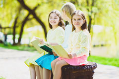 Children reading books at park. Girls sitting against trees and lake outdoor Royalty Free Stock Image