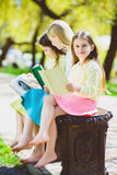 Children reading books at park. Girls sitting against trees and lake outdoor Stock Photos