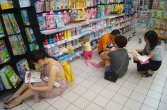 The children are reading books in the store. Stock Photography