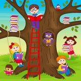 Children are reading books on a tree Stock Photography