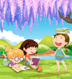 Children reading books under the tree Royalty Free Stock Photo
