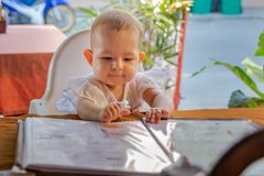 Children  reading chooses and studies the menu in the restaurant. Infant girl is sitting on a baby`s high chair in a street cafe.  royalty free stock photography