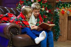 Children reading an interest book sitting on the bed against the. Decorated Christmas tree Stock Photography