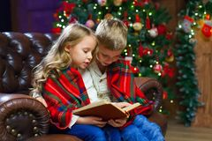 Children reading an interest book sitting on the bed against the. Decorated Christmas tree Royalty Free Stock Photos