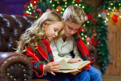 Children reading an interest book sitting on the bed against the. Decorated Christmas tree Royalty Free Stock Photo