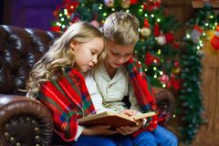 Children reading an interest book sitting on the bed against the. Decorated Christmas tree Stock Image