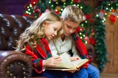 Children reading an interest book sitting on the bed against the. Decorated Christmas tree Royalty Free Stock Images