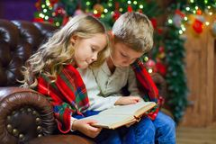 Children reading an interest book sitting on the bed against the. Decorated Christmas tree Stock Images