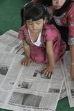 CHILDREN READING A NEWSPAPER ON A NATIONAL PRESS Stock Photos
