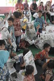 CHILDREN READING A NEWSPAPER ON A NATIONAL PRESS Royalty Free Stock Photography