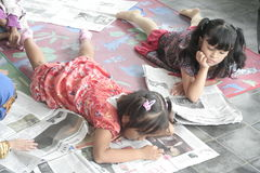 CHILDREN READING A NEWSPAPER ON A NATIONAL PRESS Royalty Free Stock Images