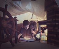 Children Reading Sparkle Book Inside Fort at Home. Two young children are reading a book together with sparkles in a tent fort at home for a story time or Royalty Free Stock Photography
