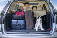 Children ready for holiday with dog in car Stock Image